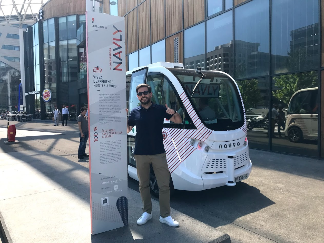 Carlos next to the NAVYA shuttle